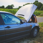 A photo of a car broken down on the side of the road with the bonnet up and a man looking at the engine